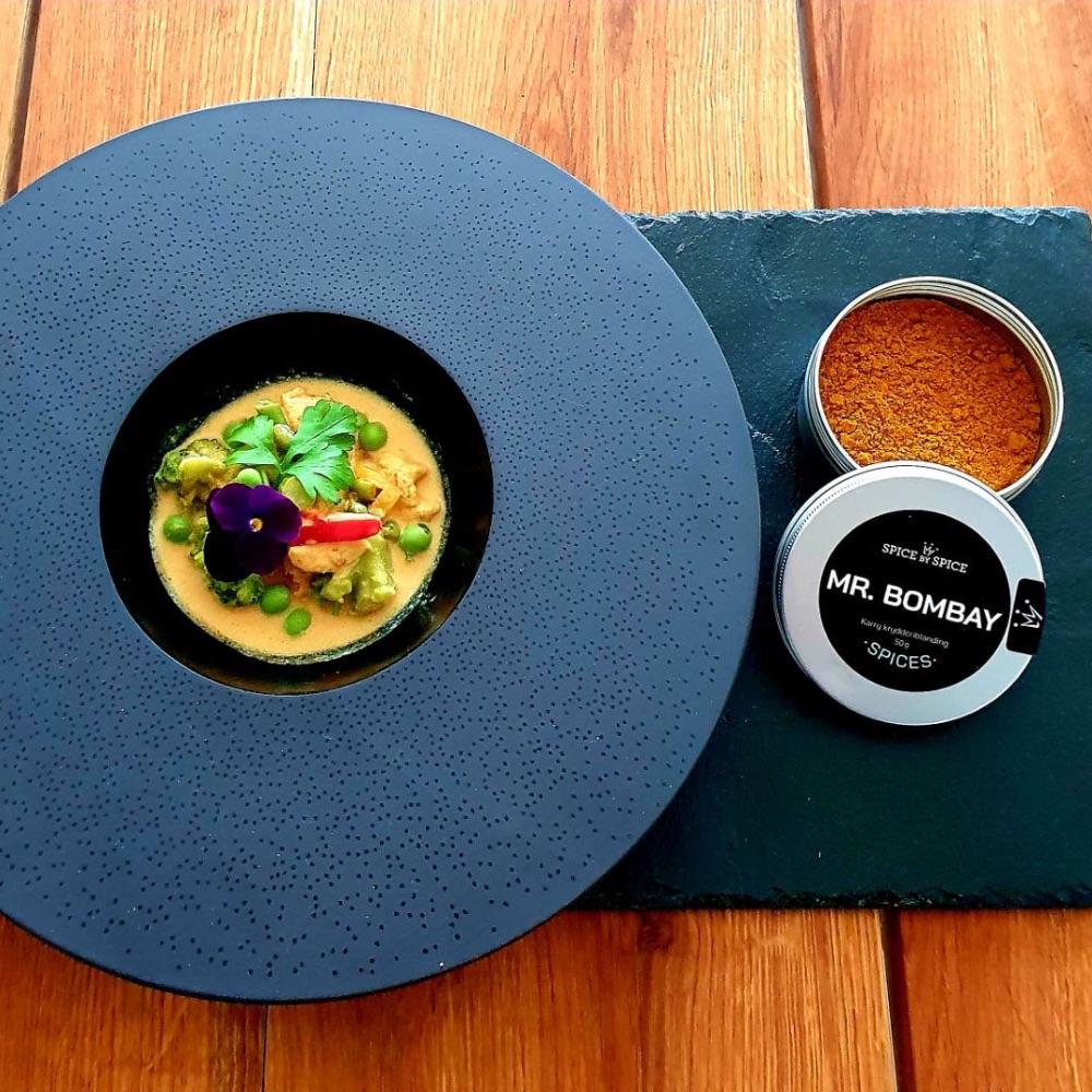 ostindisk karry på et bord sammen med en karryret anrettet i på sort tallerken